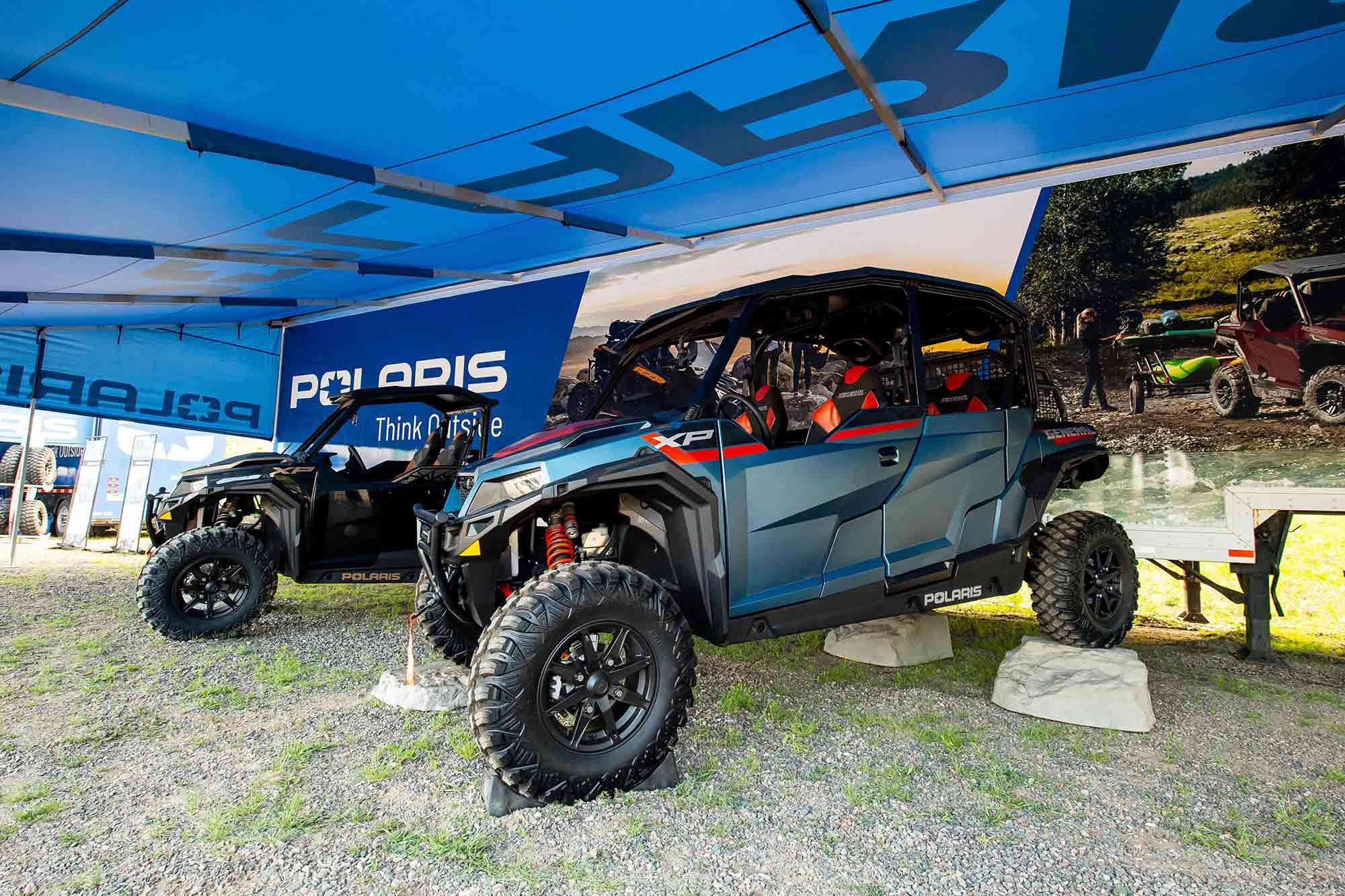 A four-door 2022 Polaris General XP 1000 Trailhead Edition models under an event tent.